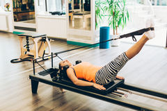 Woman stretching in pilates reformer. Woman stretching in a pilates reformer, close-up Royalty Free Stock Photos