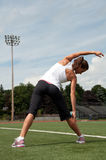 Woman Stretching On Playing Field Stock Photo