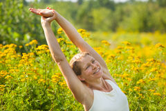 Woman stretching in ragweed flowers Stock Photos