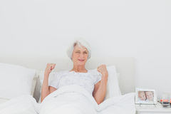 Woman stretching and raising arms in bed Stock Photo