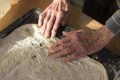 Woman Stretching Raw Pizza Crust Dough in Pan. High Angle View Senior woman Hands Stretching and Fitting Raw Thin Crust Dough for Pizza into Rectangular Pan on stock images
