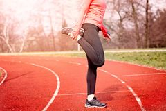 Woman stretching on a running track. Royalty Free Stock Images
