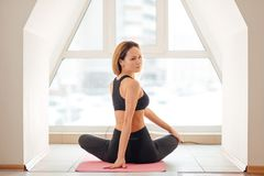 Woman stretching seated spinal twist. Young slim girl makes exercise. Fit woman stretching back exercise for spine warm up concept at home Stock Image