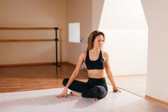 Woman stretching seated spinal twist. Young slim girl makes exercise. Yoga at home. Woman stretching seated spinal twist. Young slim girl makes exercise Royalty Free Stock Photo