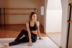 Woman stretching seated spinal twist. Young slim girl makes exercise. Yoga at home. Woman stretching seated spinal twist. Young slim girl makes exercise Stock Image
