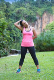 Woman stretching side of neck after exercise in outdoor park Stock Images
