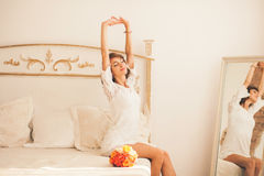 Woman stretching sitting on the bed Royalty Free Stock Image