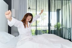 Woman stretching and sitting down on the bed while waking up in. The morning with shining light through window Royalty Free Stock Photos