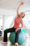Woman Stretching On Swiss Ball At Gym Royalty Free Stock Images
