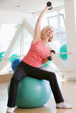 Woman Stretching On Swiss Ball At Gym Stock Photo