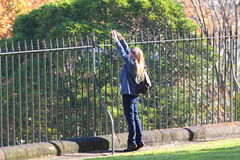 Woman stretching at iron fence Stock Photography