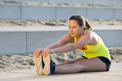 Woman stretching and touching her toes. Young, pretty looking woman in sportswear, stretching and reaching her toes with her hand during an evening jog over the Royalty Free Stock Photography