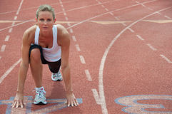 Woman Stretching At Track Starting Line stock photo