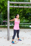 Woman stretching upper arm by wooden post in exercise park Stock Photography