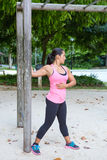 Woman stretching upper arm by wooden post in exercise park Royalty Free Stock Photo