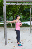 Woman stretching upper arm by wooden post in exercise park Royalty Free Stock Image
