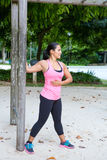 Woman stretching upper arm by wooden post in exercise park Royalty Free Stock Photography