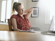 Woman Stretching While Using Laptop At Table Royalty Free Stock Photo
