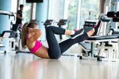 Woman stretching and warming up for her training at a gym Stock Photos