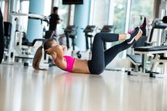 Woman stretching and warming up for her training at a gym Royalty Free Stock Images