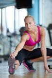 Woman stretching and warming up for her training at a gym Royalty Free Stock Photo