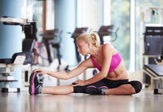 Woman stretching and warming up for her training at a gym Royalty Free Stock Image