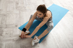 Woman stretching on the yoga mat at gym Royalty Free Stock Photo