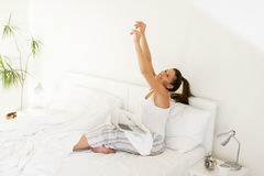 Woman stretching. Young woman stretching in bed while her lap top standing on legs royalty free stock image