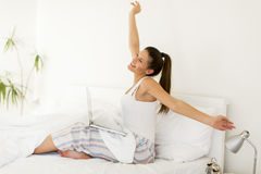 Woman stretching. Young woman stretching in bed while her lap top standing on legs royalty free stock photography