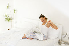 Woman stretching. Young woman stretching in bed while her lap top standing on legs royalty free stock photos