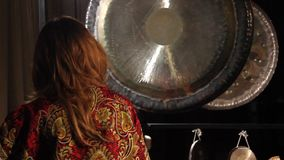 Woman strikes the gong stock video footage
