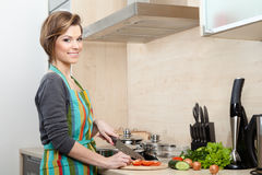 Woman in striped apron cooks Royalty Free Stock Images