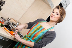 Woman in striped apron cuts vegetables Royalty Free Stock Images