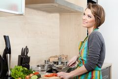 Woman in striped apron slices vegetables Royalty Free Stock Image