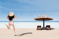 Woman in striped bikini running at beach Royalty Free Stock Images