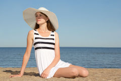 Woman in striped dress and hat sitting on the beach Stock Photo