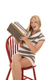 Woman striped dress stack books sit lift Stock Photos