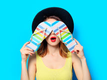 Woman with striped flip-flops. Portrait of young surprised red-haired white european woman in hat with flip-flops on blue background stock images