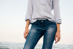 Woman in a striped shirt and blue jeans standing on sea background stock photos
