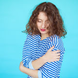 Woman in a striped shirt with eyes closed on blue background. Stock Image