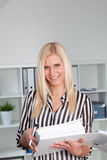 Woman in Striped Shirt Holding Binder in Office. Portrait of Smiling Blond Businesswoman Casually Dressed in Striped Shirt Holding Open Binder in Office Stock Image
