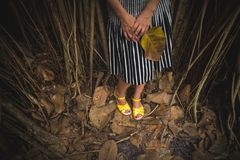 Woman in a striped skirt and yellow sandals standing in the dark tropical forest and holding a big leaf royalty free stock photos