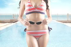 Woman in striped swimwear holds sunglasses Royalty Free Stock Photo