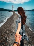 Woman in Stripes Holding Hands With Person Wearing Bracelets royalty free stock images