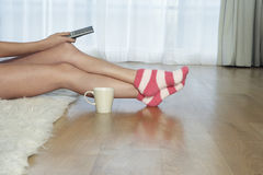 Woman In Stripey Socks With Remote Control. Lowsection of a woman in stripey socks holding remote control Royalty Free Stock Photo