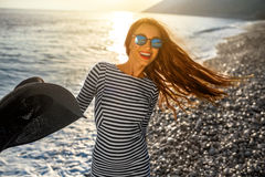 Woman in stripped dress with a hat on the beach Royalty Free Stock Images