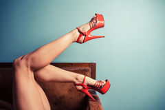 Woman in stripper heels on sofa Royalty Free Stock Image