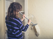 Woman stripping wallpaper Royalty Free Stock Photo