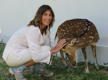 Woman strokes deer Stock Image