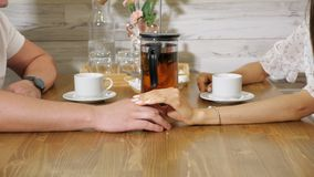 Woman strokes man hand having date in cozy restaurant. Young woman strokes gently hand of man having date at table with served tea in cozy restaurant close view stock video footage